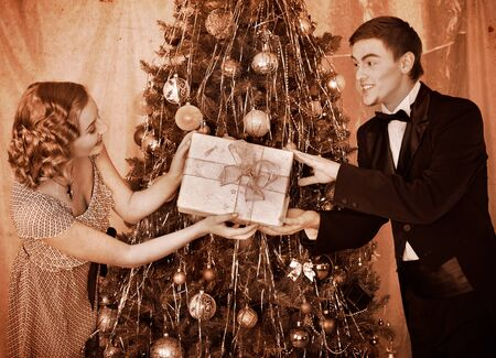 getting together: Couple on party near Christmas tree. Black and white retro.