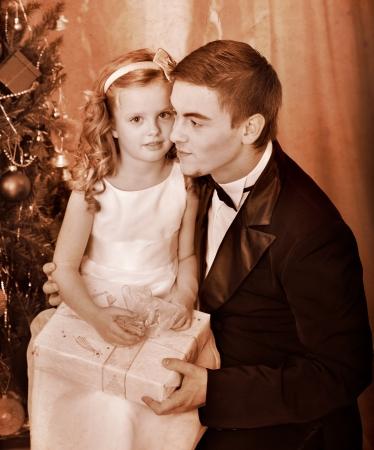 ni�os vistiendose: Ni�o con el padre recibe cerca del �rbol de Navidad. En blanco y negro retro.