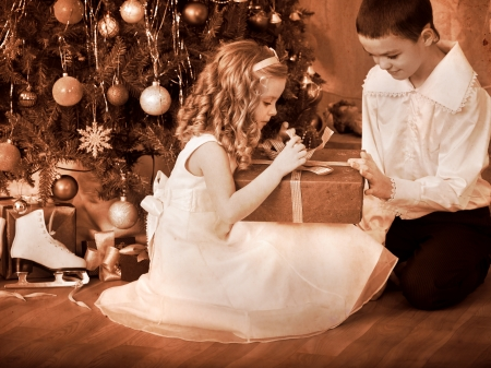 muneca vintage: Los ni�os reciben los regalos bajo el �rbol de Navidad. En blanco y negro retro. Foto de archivo