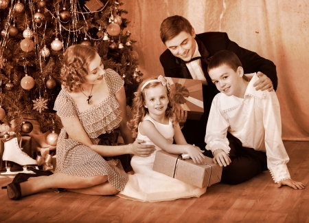 Happy family with children  receiving gifts under Christmas tree. Black and white retro. photo
