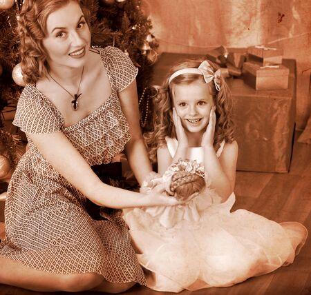 niños vistiendose: Niño con la madre de recibir regalos bajo el árbol de Navidad. En blanco y negro retro. Foto de archivo