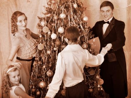 niños vistiendose: Familia feliz con los niños todo el árbol baile de Navidad. En blanco y negro retro.