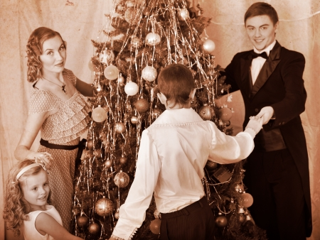 retro styled: Happy family with children round dance  Christmas tree. Black and white retro.