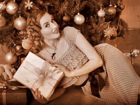 Woman receiving gifts under Christmas tree. Black and white retro. photo