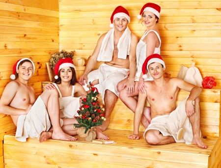 Group people in Santa hat  relaxing at sauna. photo