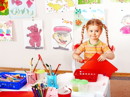 nurser: Child with scissors cut  paper  in playroom. Preschool.