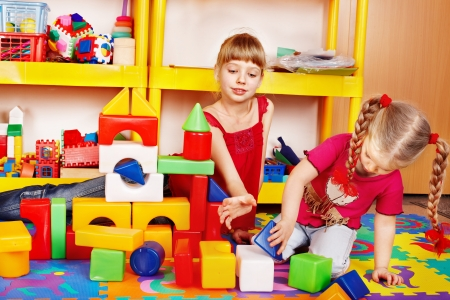 children playing with toys: Little girl plaing block and construction set in preschool. Stock Photo