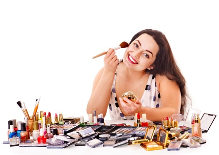 Girl applying makeup. Isolated. photo