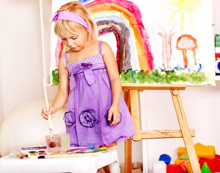 kids class: Little girl painting at easel in school. Education.