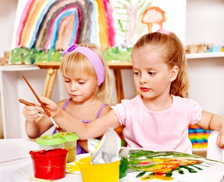 kids club: Child painting at easel in school. Stock Photo