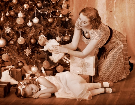 niños vistiendose: Niño con la madre recibe cerca del árbol de Navidad. En blanco y negro retro. Foto de archivo