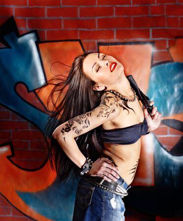 tatouage sexy: Femme avec l'art du corps aganist mur de briques de graffiti.