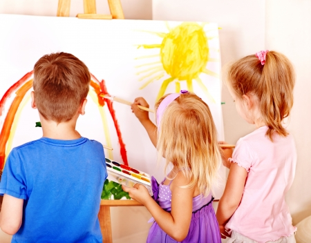 Group children painting at easel in school. photo