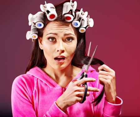 hair curlers: Happy woman wear hair curlers holding scissors.