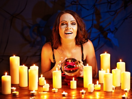 predict: Woman holding scrying ball and candle.