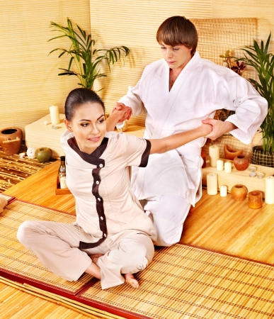 male massage: Male masseur doing massage young woman in bamboo spa. Stock Photo
