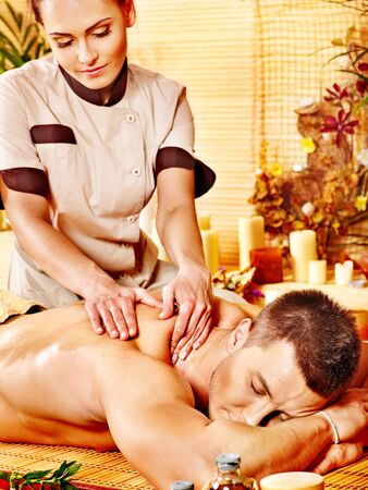 Man getting massage in bamboo spa. Female therapist. photo