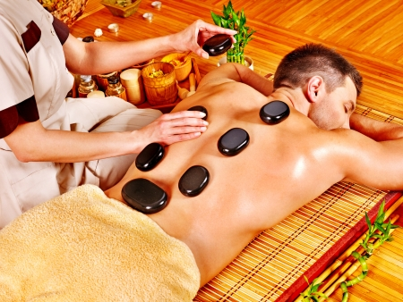 health resort treatment: Man getting stone therapy massage in bamboo spa.