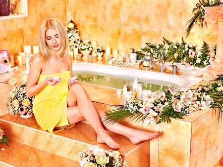 Blonde woman relaxing at flower water spa. photo