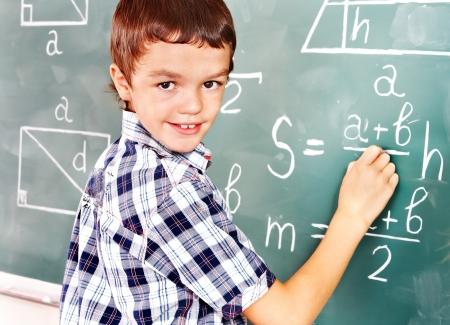 Teen school child near blackboard  in classroom. Stock Photo - 17532073