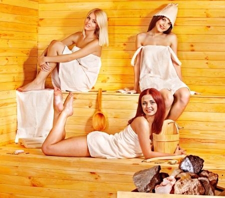 Happy girlfriends relaxing in sauna. photo