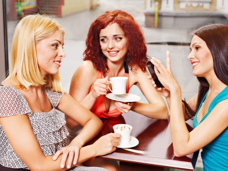 social life: Three young women at laptop drinking coffee in a cafe. Stock Photo