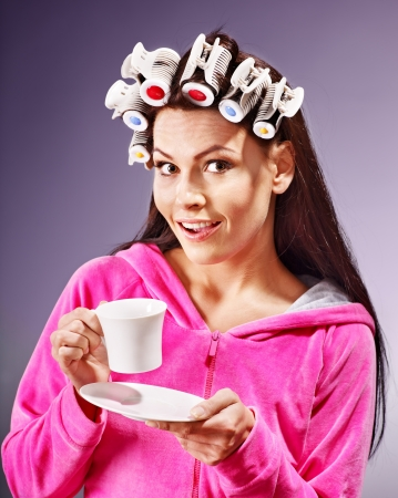 hair curlers: Woman wear hair curlers on head holding cup of coffee. Stock Photo
