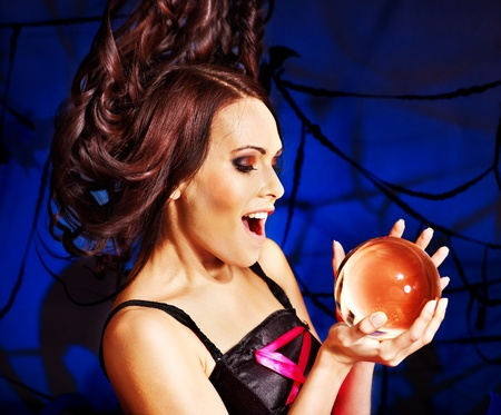 Young woman  with crystal ball. Halloween. photo