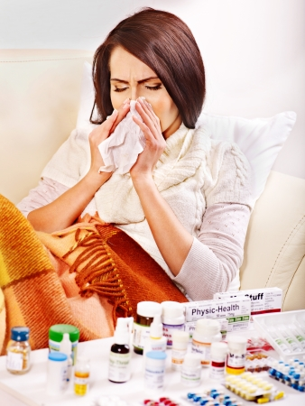 cold remedy: Woman with remedy having  flue in bed. Isolated. Stock Photo