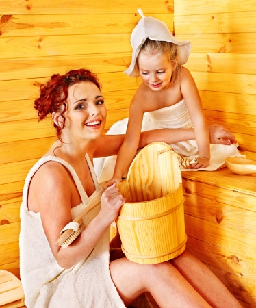 Happy family with child relaxing at sauna. photo