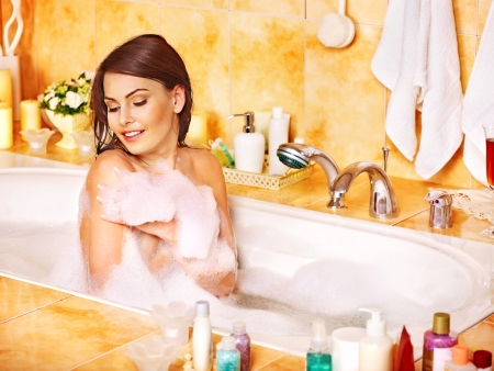 Woman relaxing at water in bubble bath. photo