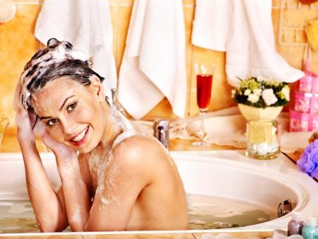mujer bañandose: La mujer lava su cabeza en el baño de casa.