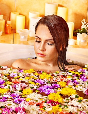 lying in bathtub: Woman relaxing at water spa.