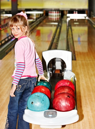 Child girl in with bowling ball learn game. photo