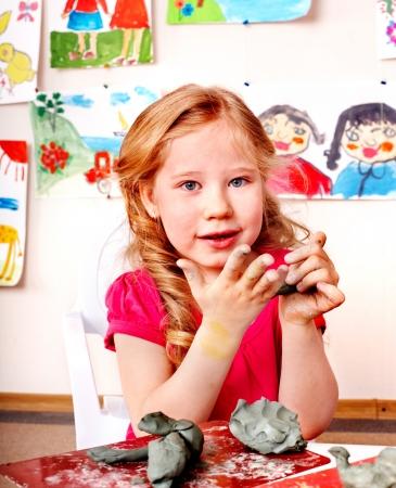 nurser: Child girl with clay in play room. Preschool.