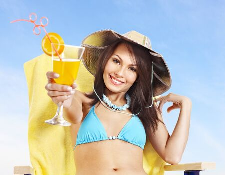 Young woman in bikini drink juice through a straw. photo