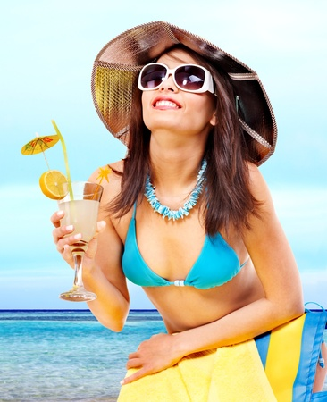 Woman in bikini drinking alcohol coctail through a straw. photo