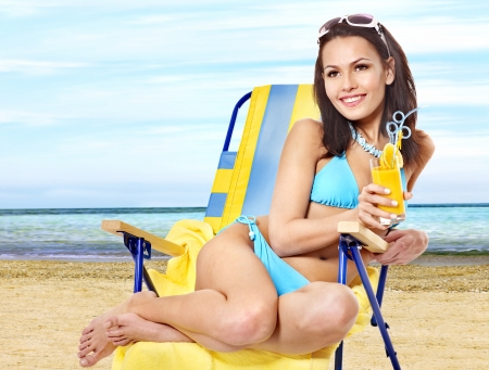 Young woman in bikini drink juice through a straw on beach. photo