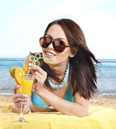 Young woman in bikini drink juice through a straw. Stock Photo - 17753873