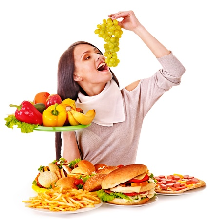 Woman choosing between fruit and hamburger. Isolated. Stock Photo - 17698025