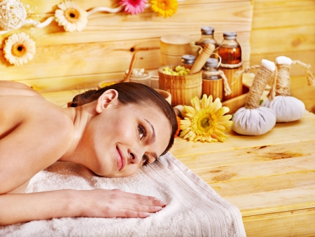 bamboo therapy: Woman getting herbal ball massage  in spa.