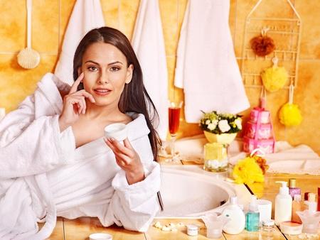 Woman applying moisturizer at bathroom. Stock Photo - 17701725