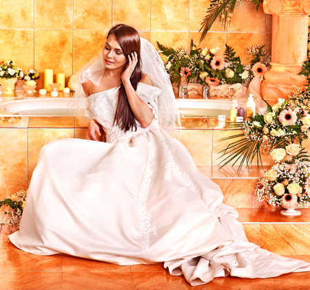 wife of bath: Woman wearing wedding dress at spa.