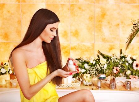 bath cream: Woman applying moisturizer at bathroom.