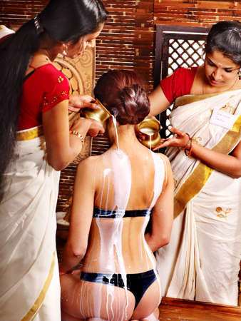 Woman having Ayurvedic spa treatment. Pouring milk. photo