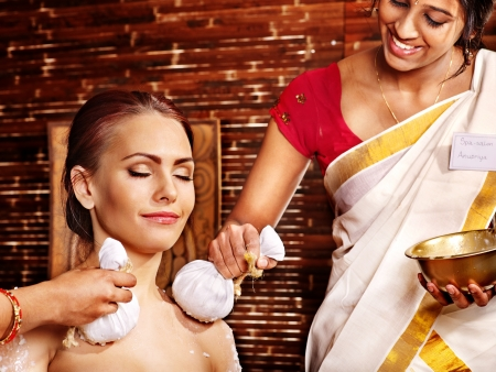 ayurveda: Woman having ayurvedic massage with pouch of rice.