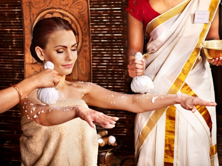 panchakarma: Woman having ayurvedic massage with pouch of rice.