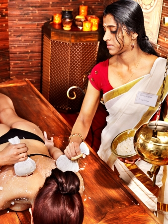 Woman having ayurvedic massage with pouch of rice. Stock Photo - 17701742