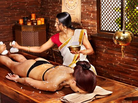 Woman having massage with pouch of rice. Ayurveda treatment. photo