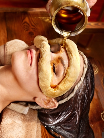 Woman having facial oil eyes mask at ayurveda spa. photo
